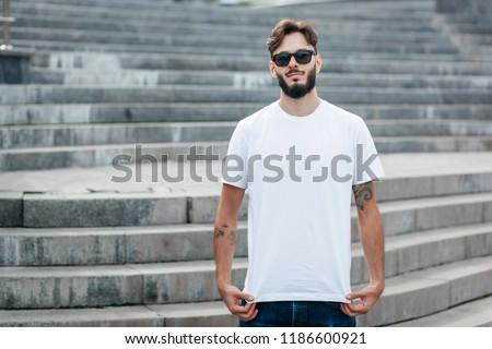 A young stylish man with a beard in a white T-shirt and glasses. Street photo #1186600921