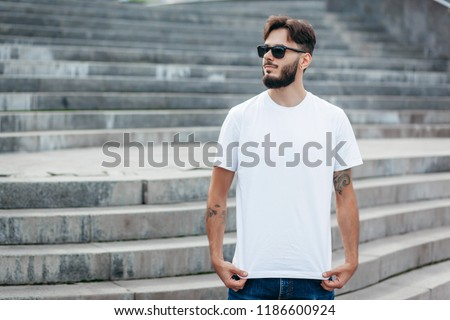 A young stylish man with a beard in a white T-shirt and glasses. Street photo #1186600924
