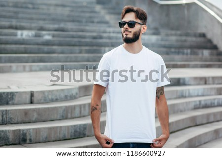 A young stylish man with a beard in a white T-shirt and glasses. Street photo #1186600927