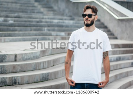 A young stylish man with a beard in a white T-shirt and glasses. Street photo #1186600942