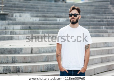 A young stylish man with a beard in a white T-shirt and glasses. Street photo #1186600960