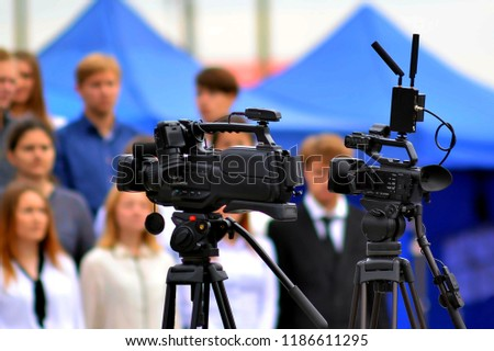 a video camera stands on a tripod at a solemn event #1186611295