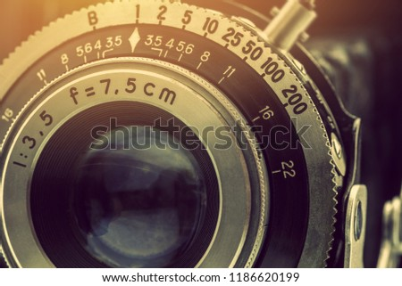 Close-up detailed photo of the optical lens of a nostalgic old retro 35mm negative film camera with f-stop and focal length number, retouched by removing out the dust and rust, vintage filter effect. #1186620199