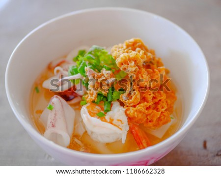 Thai street food is a popular.Noodle Soup Thai Style with squid  shrimp  in white bowl on wooden. #1186662328