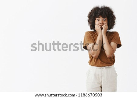 Studio shot of scared african american teenage girl in stupor popping eyes at camera and covering mouth not to scream with hands being terrifyied and frightened trembling from fear and shock #1186670503