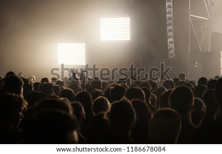 Crowd at concert - Cheering crowd in bright colorful stage lights #1186678084