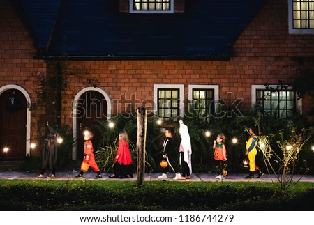 Group of kids with Halloween costumes walking to trick or treating #1186744279