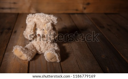 Child abuse concept. Teddy bear covering eyes, dark empty background, copy space #1186779169