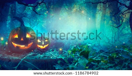 Halloween theme with pumpkins and dark forest. Scary Halloween design on table