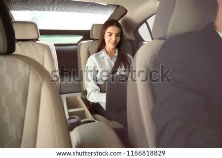 Young businesswoman with laptop in car #1186818829