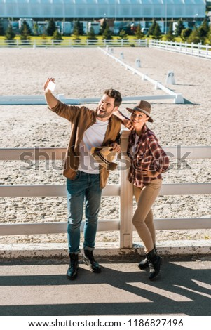 smiling stylish cowboy and cowgirl in casual clothes taking selfie with smartphone at ranch #1186827496