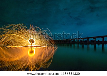 The Fire Burning steel wool spinned in the lake near the bridge at the Pa Sak Jolasid Dam Showers of glowing sparks from spinning steel wool very nice and beautiful at night time at Lopburi, Thailand