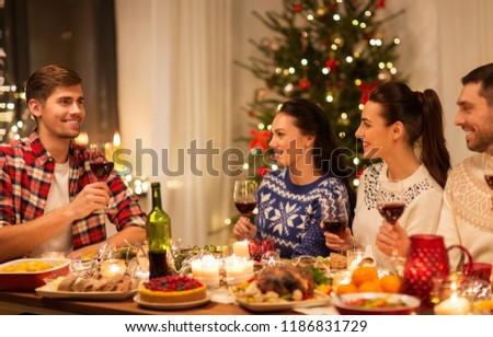 holidays and celebration concept - happy friends having christmas dinner at home and drinking red wine #1186831729