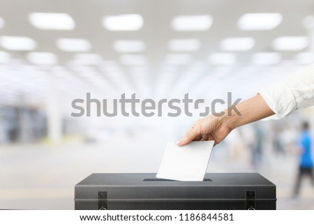 The hand of woman holding ballot paper for election vote concept at place election background. #1186844581