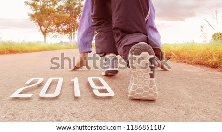 2019 symbolises the start into the new year.Start of people running on street,with sunset light.Goal of Success #1186851187