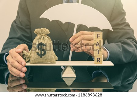 Fair value pricing / debt or money at fair value concept : Dollar money bags on a basic balance scale, businessman as an insurer protects or guards his properties, depicts protecting high risk assets #1186893628