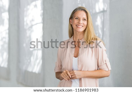 Cheerful mature woman in casual looking away indoor. Successful senior woman smiling and standing confidently. Portrait of happy beautiful lady in a pink shirt with toothy smile standing. #1186901983