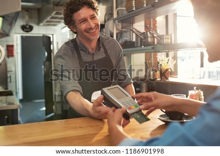 Woman paying by credit card and entering pin code on reader holded by smiling barista in cafeteria. Customer using credit card for payment. Mature cashier accepting payment over nfc technology. #1186901998
