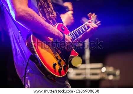 Guitarist playing on electric bass guitar on stage. Colorful, soft focus and blur background. #1186908838