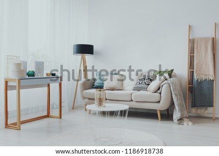Couch with pillows between lamp and ladder in white living room interior with table. Real photo #1186918738
