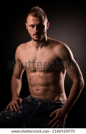 Young muscular man shows his muscles and toned torso.Studio photo sessin,potrait with the black background.He has short hair and short beard.Fitness. #1186920970