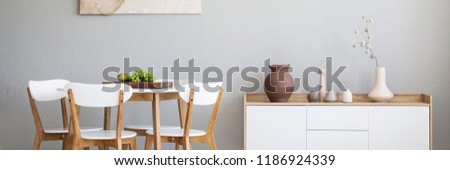 Panorama of a cutting board with fruit on a simple white table with wooden chairs around in a bright dining room interior with gray walls #1186924339