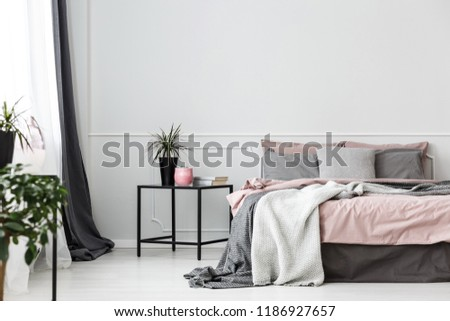 Black, box frame side table next to a cozy bed with gray blankets and pink sheets in an elegant bedroom interior #1186927657