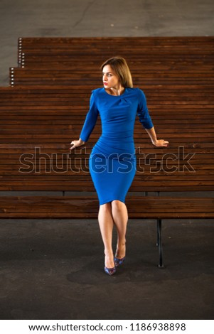 Young beautiful calm blonde woman in blue dress in an empty auditorium #1186938898
