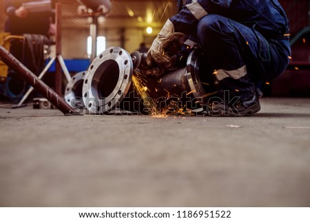 Professional welders in protective uniform and mask welding metal pipe in workshop. #1186951522