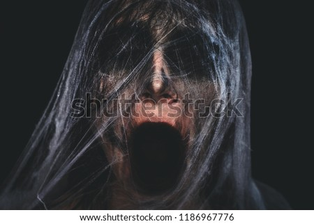Screaming creepy character covered with spiderweb on black background. Halloween spooky creature portrait with copy space Royalty-Free Stock Photo #1186967776