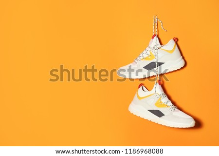 Pair of stylish sneakers hanging on color wall, space for text #1186968088