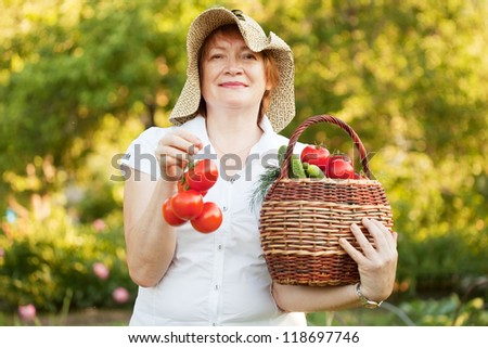 Happy mature woman with vegetables in garden #118697746