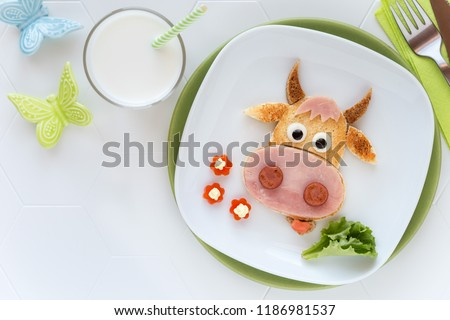 Fun food for kids - cute cow shaped sandwich with ham sausages served with a glass of milk for breakfast or dinner #1186981537