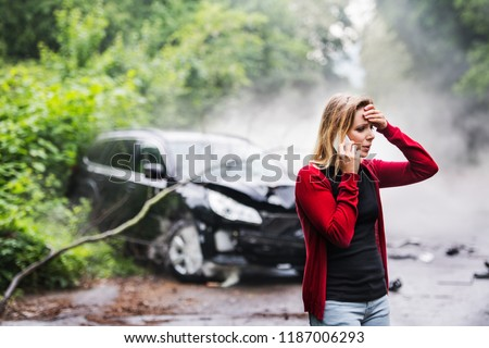 A young woman with smartphone by the damaged car after a car accident, making a phone call. Royalty-Free Stock Photo #1187006293