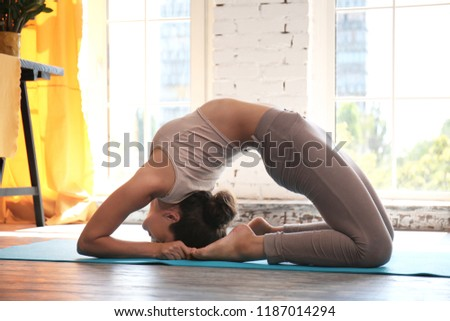 Sporty woman practicing yoga at home #1187014294