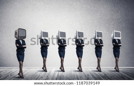 Business women in suits with monitors instead of their heads keeping arms crossed while standing in a row and one at the head with old TV in empty room against gray wall on background. #1187039149