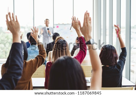 Group of business people raise hands up to agree with speaker in the meeting room seminar Royalty-Free Stock Photo #1187069845