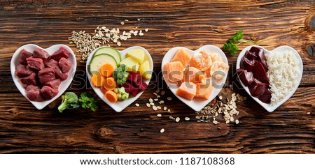 Panorama banner of healthy fresh ingredients for pet food in individual heart-shaped bowls viewed from overhead with chopped raw beef, liver and chicken , mixed vegetables and rains on rustic wood #1187108368
