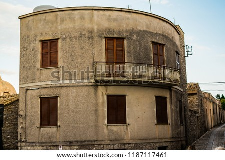 Interesting, strange, rounded house building in Erice, Sicily, Italy. Weird type of architecture, with the balcony on the 1st floor.  In the background narrow, Italian city street. Ancient style.  #1187117461