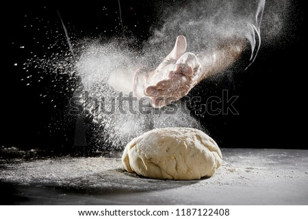 Chef scattering flour while kneading dough for bread #1187122408