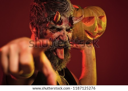 Halloween demon point finger with jack o lantern. Man devil hold pumpkin on red background. Darkness and light concept. Satan show tongue with bloody horns, beard, blood, wounds. Trick or treat. #1187125276