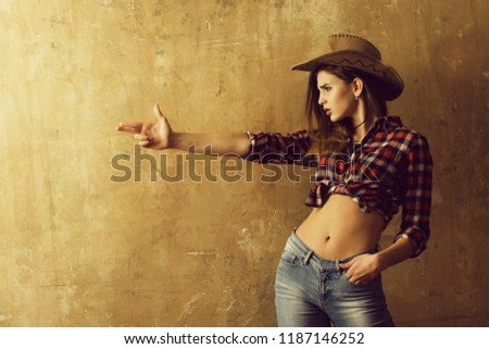 cowboy girl or pretty woman with blond, long hair in stylish hat and red plaid shirt showing finger gun, hand gesture, on beige wall background. Nonverbal communication, gunfighter