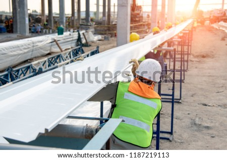 Construction worker installation metal roof sheet at new building construction site #1187219113