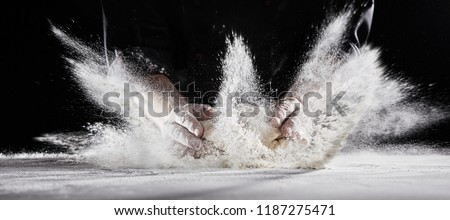 White flour flying into air as pastry chef in black suit slams ball dough on white powder covered table #1187275471