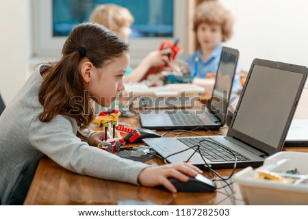 Girl using a laptop while assembling a robot from plastic bricks. STEM Education for kids. #1187282503