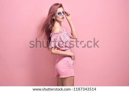 Young Pretty Blonde Girl posing in Studio. Beautiful woman in Stylish romantic Summer Outfit, Trendy Hairstyle, Fashion Sunglasses. Portrait Sexy adorable Lady on Pink vanilla background #1187343514