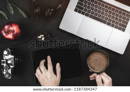 Man using app with digital tablet. Top view of laptop and headphones on a black table, flat lay #1187384347