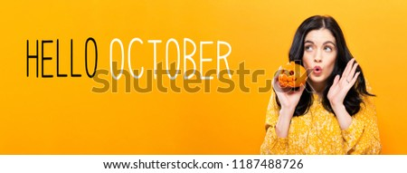Hello October with young woman holding a pumpkin #1187488726