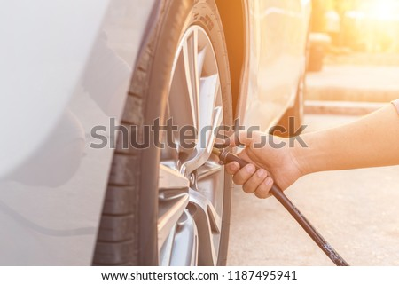 Man checking air pressure and filling air in the tires of his car #1187495941