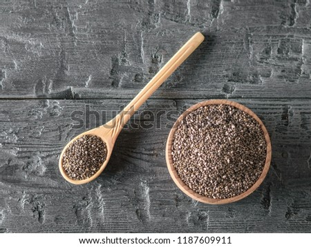 Wooden bowl and spoon with black Chia seeds on rustic table. The view from the top. Flat lay. #1187609911